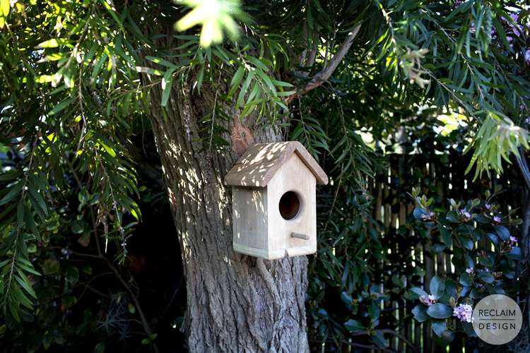 Our reclaimed wood birdhouse at home in a garden | Reclaim Design